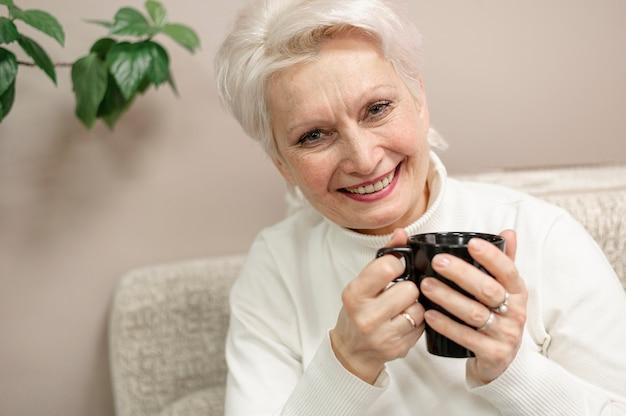 Smiley starsza kobieta pije kawę w domu
