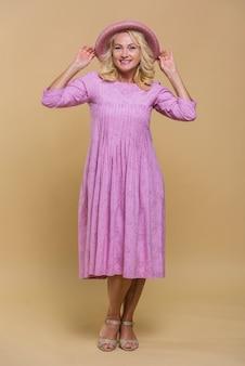 Smiley starsza kobieta pozuje w różowej sukni