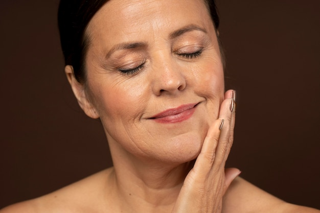 Smiley starsza kobieta pozuje z makijażem