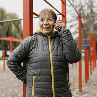 Smiley starsza kobieta rozmawia przez telefon na zewnątrz