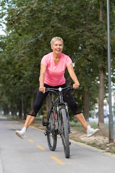 Smiley starsza kobieta świetnie się bawi na rowerze na świeżym powietrzu