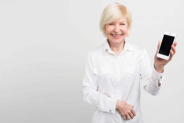 Smiley starszy kobieta trzyma w ręku nowy smartfon. nauczyła się go używać. pasjonuje ją internet i nowe technologie.
