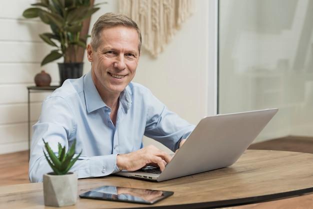 Smiley starszy mężczyzna patrzeje na jego laptopie
