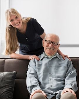 Smiley starszy mężczyzna z pielęgniarką w domu opieki