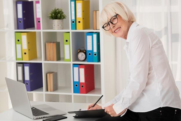 Smiley starszy obsiadanie na jej biurze