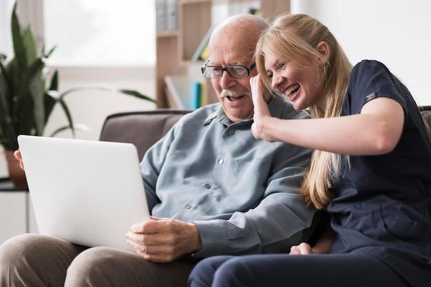 Smiley starzec i pielęgniarka o rozmowie wideo na laptopie