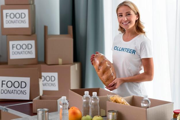 Smiley wolontariuszka pomagająca w darowiznach żywności
