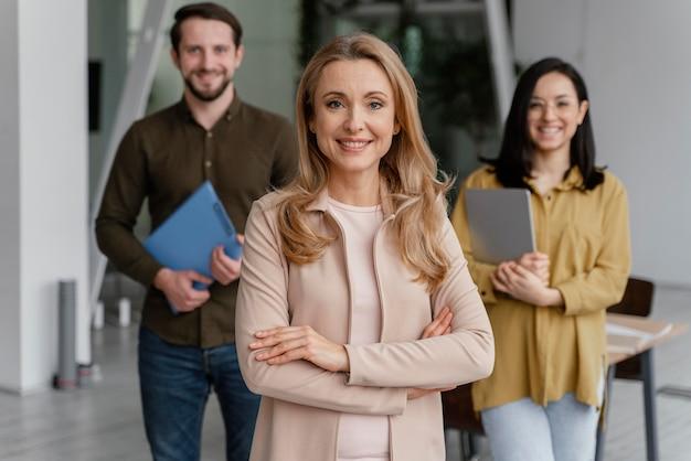 Smiley współpracownicy pozują razem w biurze