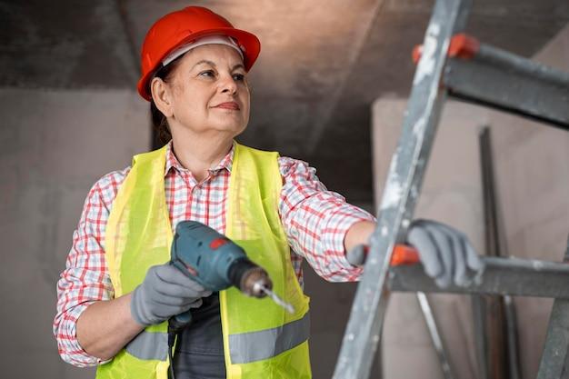 Smiley żeński pracownik budowlany z wiertłem