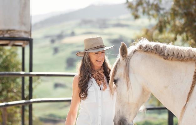 Smiley żeński rolnik z koniem na ranczo