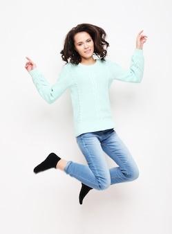 Smilg młoda kobieta skacze w powietrzu nad bielem