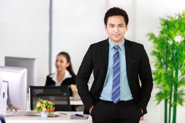 Smiling azjatyckiego biznesmena stoj?cego trzymaj?cego r?k? biurko i businesswoman pracuje komputer stacjonarny z t?em w biurze. koncepcja szczęśliwa praca.