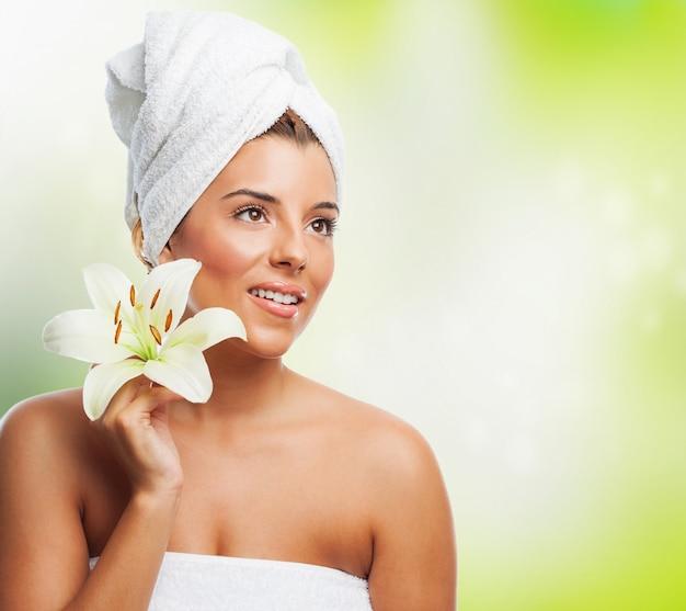 Smiling model z ręcznikiem i lilia