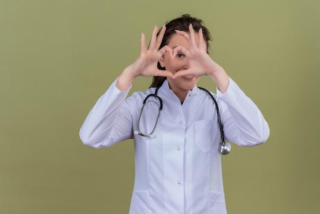 Smilinng lekarz młoda dziewczyna ubrana w medyczną fartuch noszenia stetoskopu pokazuje gest serca na zielonym tle
