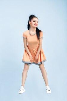 Smilling młoda brunetka kobieta w pomarańczowej sukience na niebiesko