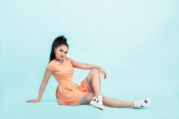 Smilling młoda brunetka kobieta w pomarańczowej sukience siedzi na podłodze na niebiesko