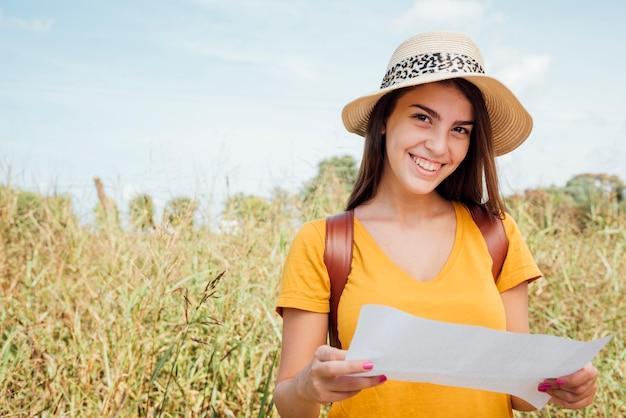 Smily kobieta jest ubranym kapelusz patrzeje bezpośrednio przy kamerą