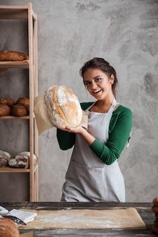 Smling młodej damy piekarniana pozycja przy piekarni mienia chlebem.