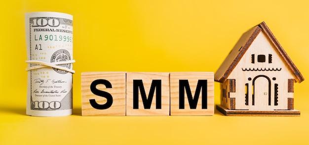 Smm z miniaturowym modelem domu i pieniędzmi na żółtym tle. inwestycje, nieruchomości, dom, mieszkanie, zarobki, koncepcja finansowa