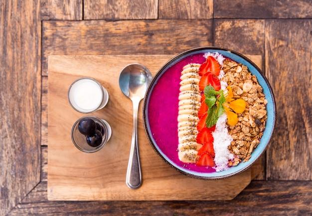Smocza miska smoothie owocowa z truskawkami, muesli, nasionami chia i bananem na drewniane tła. widok z góry, miejsce na tekst.