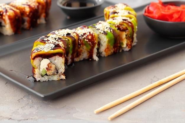 Smocze roladki sushi z węgorzem i awokado na szarym stole