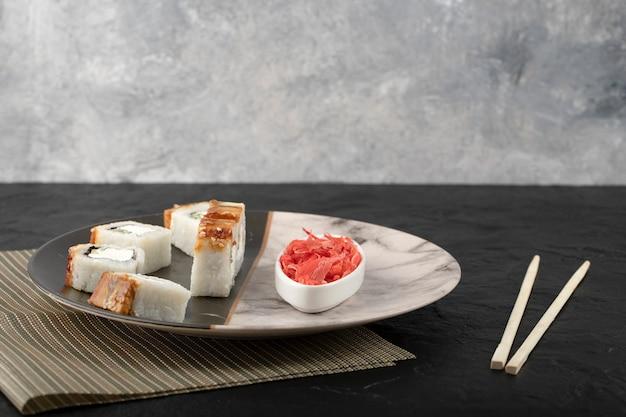 Smocze sushi roladki z węgorzem i marynowanym imbirem na marmurowym talerzu