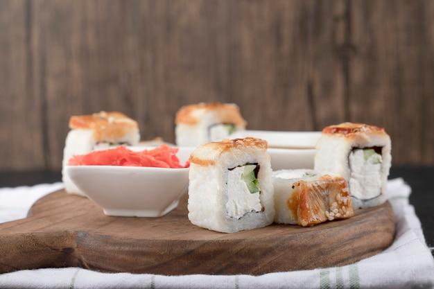 Smocze sushi rolki z węgorzem i marynowanym imbirem na drewnianej desce