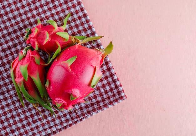 Smoczy owoc na różowym i piknikowym materiale, leżący na płasko.