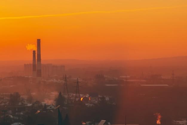 Smog wśród sylwetek budynków na wschód słońca. smokestack w jutrzenkowym niebie. zanieczyszczenie środowiska podczas zachodu słońca. szkodliwe opary ze stosu nad miastem. mgła tła miejskiego z ciepłym pomarańczowym żółtym niebem.