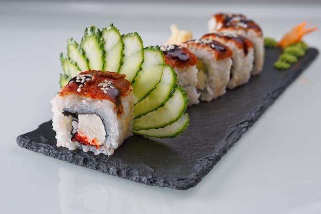 Smok roll sushi, na czarnym kamieniu, na białym tle
