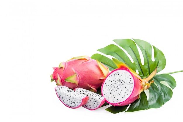 Smoka owocowy tropikalny, pitaya plasterek na zielonych liściach odizolowywających na bielu, z ścinek ścieżką