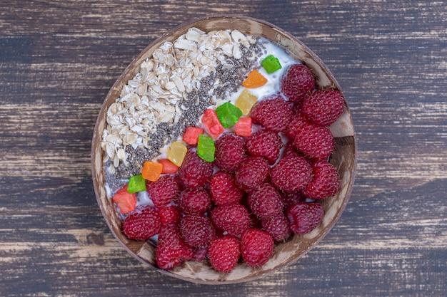 Smoothie w misce kokosowej z malinami, płatkami owsianymi i nasionami chia
