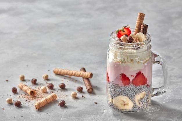 Smoothie w szklankach z owocami truskawka, banan, jagoda, płatki owsiane i chia