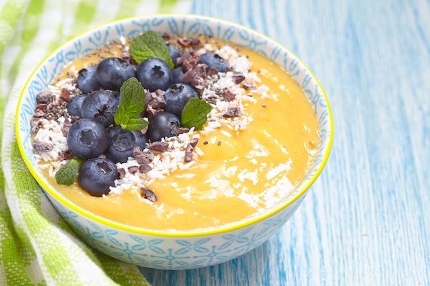 Smoothie z mango, pomarańczą i bananem ozdobione jagodami