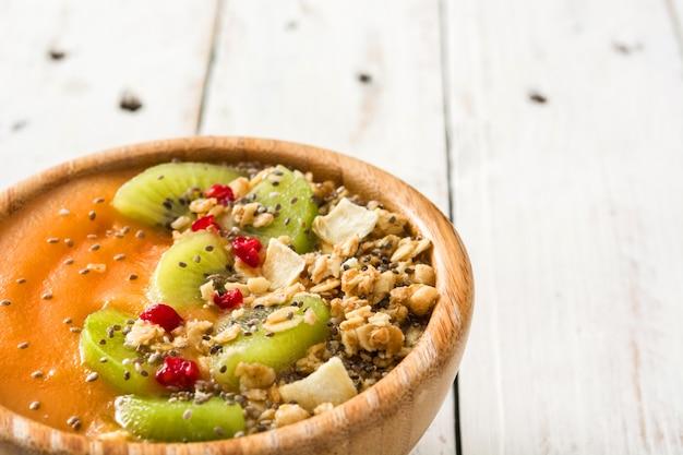 Smoothie z płatków owocowych i chia na białym drewnianym stole