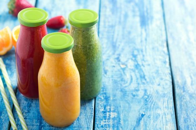 Smoothie ze świeżych truskawek, pomarańczy i brokułów w butelkach z owocami i warzywami