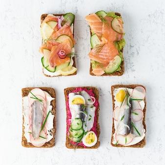 Smorrebrod pikantne ryby, zestaw pięciu tradycyjnych duńskich kanapek. czarny chleb żytni z anchois, burakami, rzodkiewką, jajkami, łososiem, twarogiem, ogórkiem, awokado na szarym kamiennym stole, widok z góry
