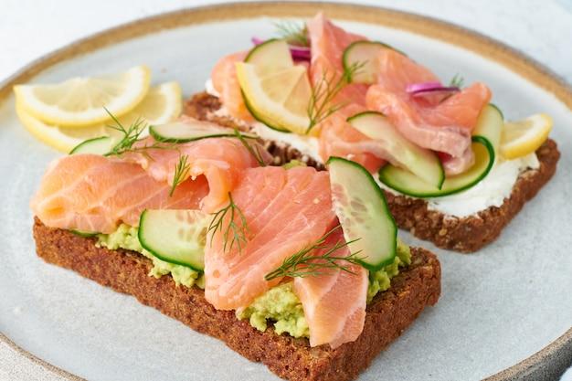Smorrebrod - tradycyjne duńskie kanapki. czarny chleb żytni z łososiem, twarogiem, ogórkiem, awokado na drewnie