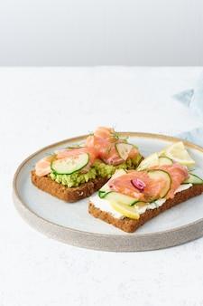 Smorrebrod - tradycyjne duńskie kanapki. czarny chleb żytni z łososiem, twarogiem