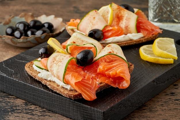Smorrebrod - tradycyjne duńskie kanapki. czarny chleb żytni z łososiem, twarożkiem