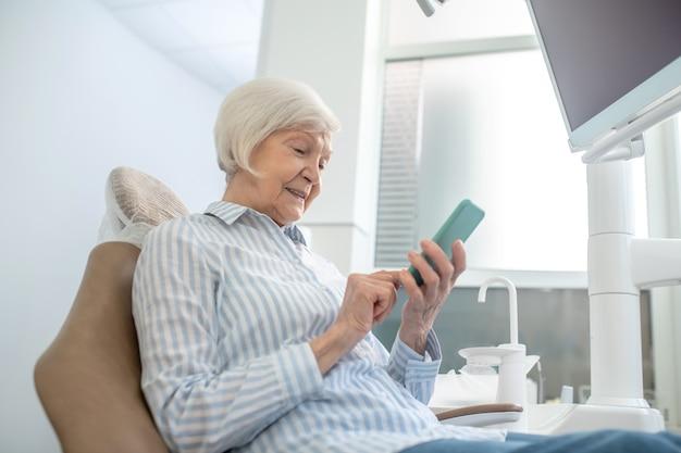Sms-y. starsza kobieta siedzi w gabinecie dentystycznym i używa swojego smartfona