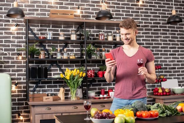 Sms-y z chłopakiem. brodaty chłopak trzymający smartfona i wysyłający sms-a do swojej uroczej kobiety zapraszającej ją na obiad