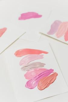 Smugi szminki w pastelowych kolorach na arkuszach papieru