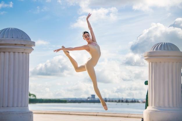 Smukła baletnica w pointach i stroju ślubnym skacze na tle morza