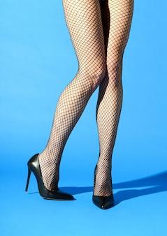 Smukła kobieta ubrana w seksowne czarne kabaretki i dopasowane szpilki