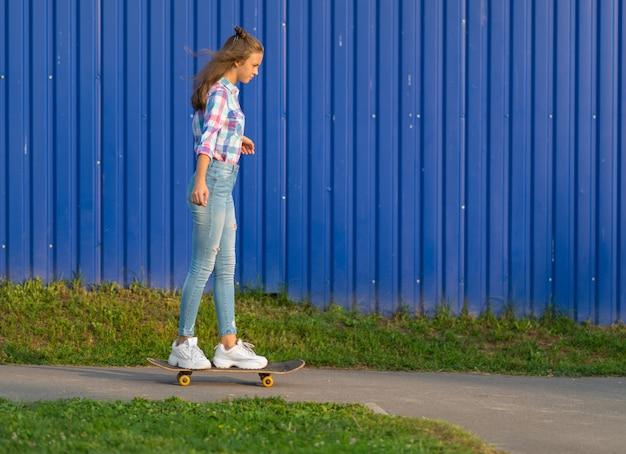 Smukła, modna młoda kobieta jeździ na deskorolce w mieście wzdłuż ścieżki przed kolorową niebieską ścianą w wieczornym świetle
