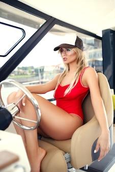 Smukła, seksownie opalona kobieta w czapce z okularami przeciwsłonecznymi i czerwonym kostiumem kąpielowym siedzi za sterami na jachcie
