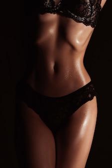 Smukła sylwetka dziewczyny w czarnej bieliźnie. atletyczne ciało młodej kobiety o opalonej skórze