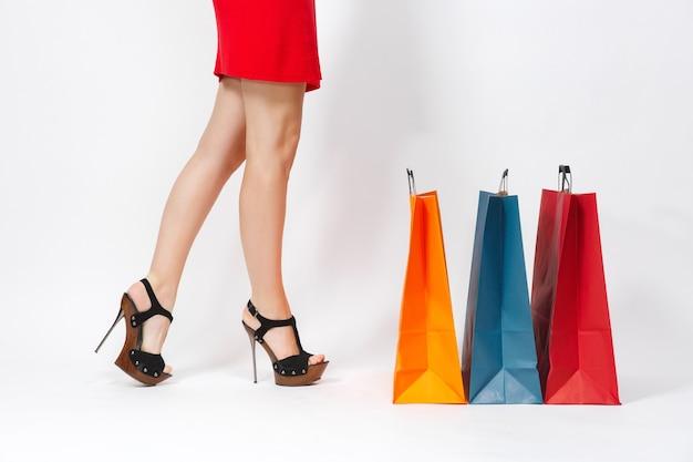 Smukłe, długie kobiece nogi w czarnych sandałach, kaukaski kobieta w czerwonej sukience stojącej w pobliżu multi kolorowych pakietów z zakupami po zakupach na białym tle. skopiuj miejsce na reklamę.