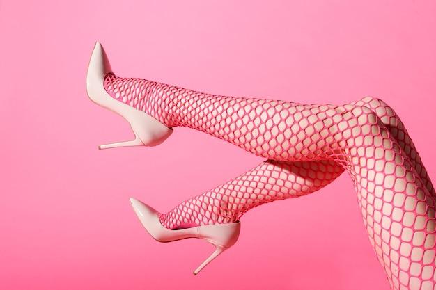 Smukłe kobiece nogi uniesione w seksowne różowe kabaretki i dopasowane szpilki